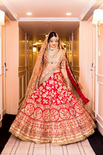 Bride showing off red and gold bridal lehenga
