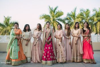 Photo of Bride standing with bridesmaids