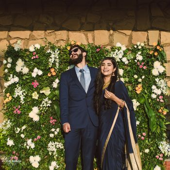 Engagement decor idea with couple standing against flower wall