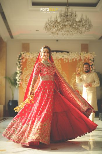 Twirling bride in red and gold lehenga