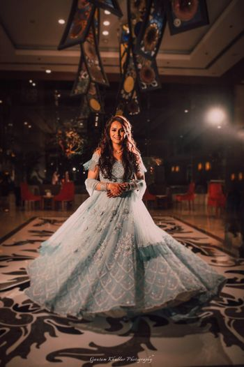 Pretty bride twirling in a pastel blue lehenga