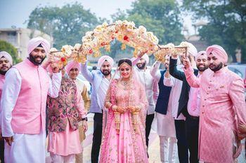 Sikh bride in light pink entering under unique phoolon ki chadar
