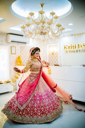 Bride twirling in red and pink ombre lehenga