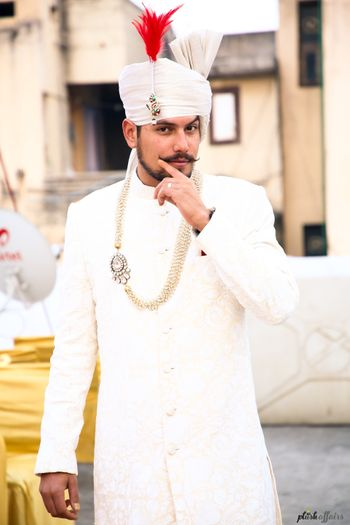 Groom wearing white sherwani jewellery and turban with red feather