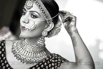 Black and white shot of bride adjusting nosering