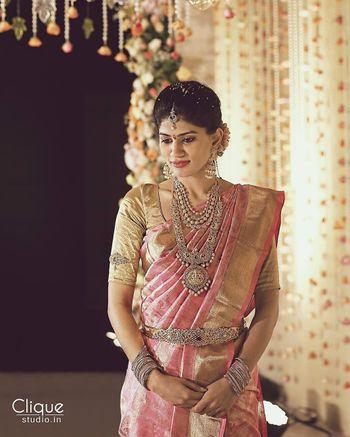South Indian bride wearing silver jewellery with pink kanjivaram