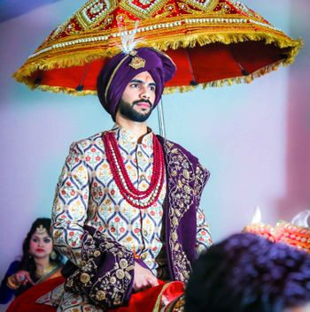 Groom wearing purple sherwani and turban with red beaded necklace
