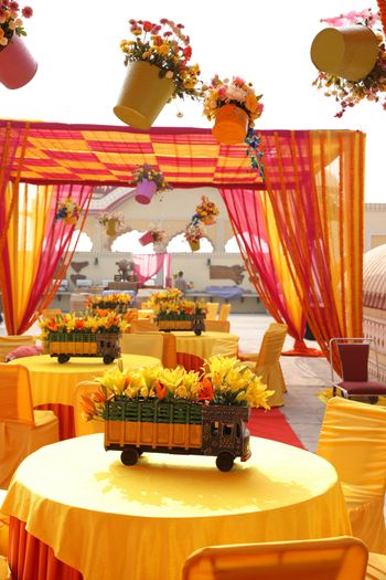 Photo of Hanging flower pots and decorated mini trucks as props for mehendi decor