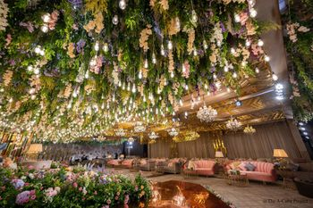 Lush greens, suspended bulbs and florals for the ceiling decor.