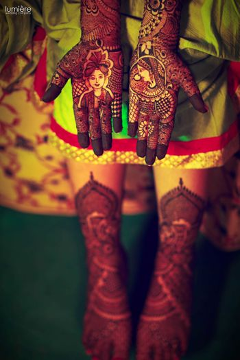 Photo of Mehendi design with bride and groom portraits on hands