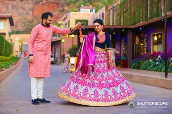 Bride in bright pink and blue threadwork lehenga for mehendi