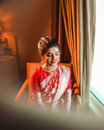 A marathi bride dressed in a red and gold saree.