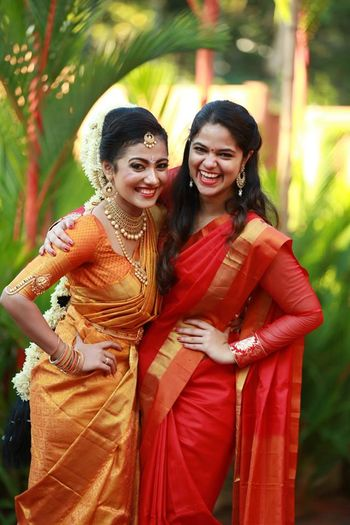 South Indian bride with sister in red silk saree