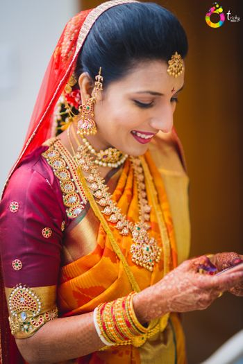 Photo of South Indian bride wearing orange kanjivaram with embellished maroon blouse