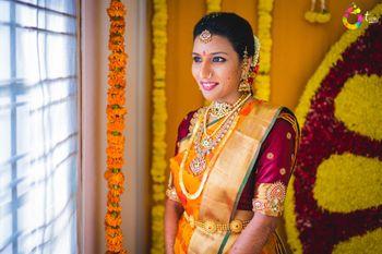 Photo of Gold and orange kanjivaram with contrasting maroon blouse