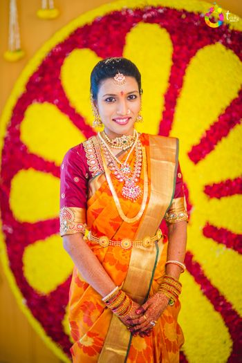 Photo of South Indian bride wearing orange and gold kanjivaram saree