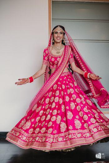 Bride twirling in a pink lehenga.