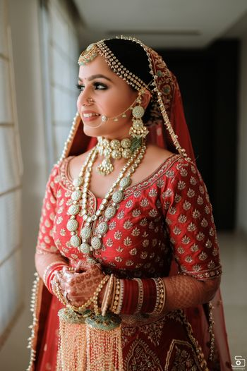 Photo of Bride dressed in red lehenga with contrasting jewellery.