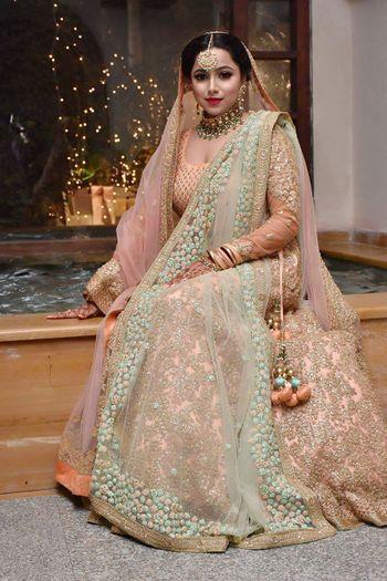 Photo of Bride in pastel orange and mint lehenga