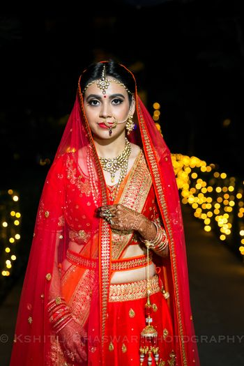Bride in bright lehenga with waist belt and kaleera