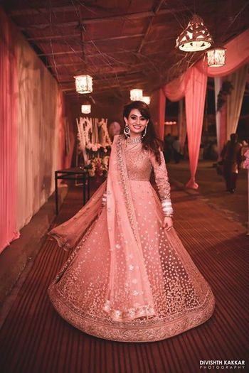 Twirling bride in shimmery peach and gold net anarkali