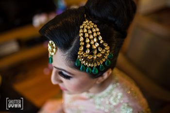 Bride wearing large jhoomer with green stones