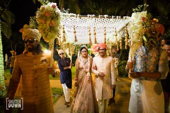 Bride entering under unique phoolon ki chadar with kaleere