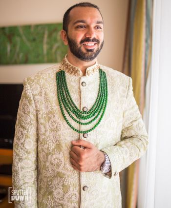 Groom wearing light green sherwani with contrasting necklace