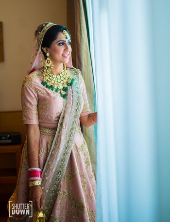 Bride looking out of window in pink lehenga with green jewellery