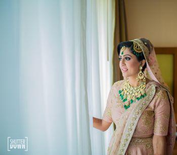 Bride wearing light pink lehenga and green contrasting jewellery