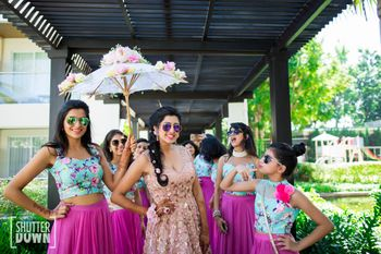 Bride entering with matching bridesmaids under floral umbrella