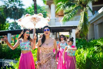 Dancing entry of bride with bridesmaids holding lace umbrella