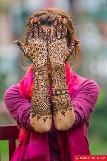 Modern bridal mehendi design with bride holding her hands up