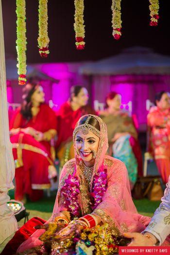Happy bride shot wearing light pink lehenga