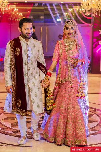 Bride in coral lehenga with gold sequin work and pink kaleere
