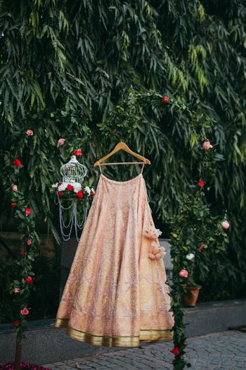 Peach threadwork lehenga on hanger with birdcage