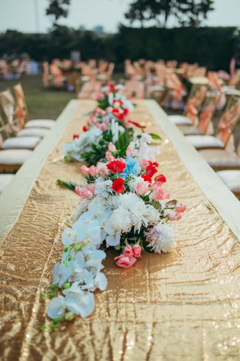 Photo of Gold table runner with sequins and floral arrangement