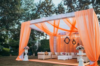 Photo of Orange and white mandap decor with drapes for destination wedding