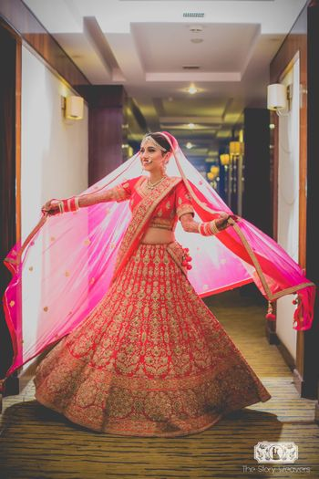 Photo of Bride twirling and posing with dupatta in red lehenga