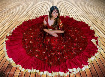 Bride with maroon flared lehenga on the floor