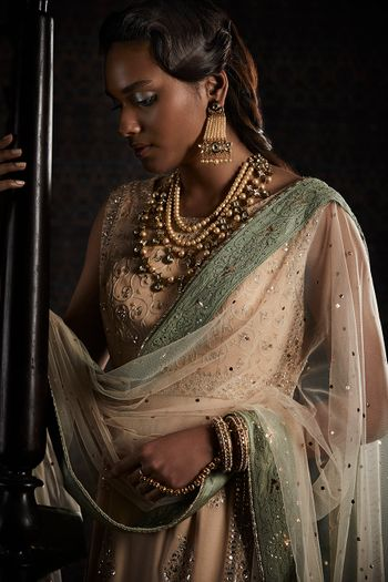 Photo of Dusky bride wearing olive green and beige lehenga