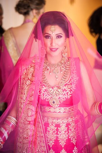 Bride in bright pink lehenga with dupatta as veil