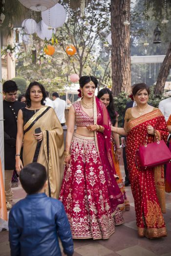 Photo of Bride in red and white lehenga with sleeveless blouse and single dupatta draping style