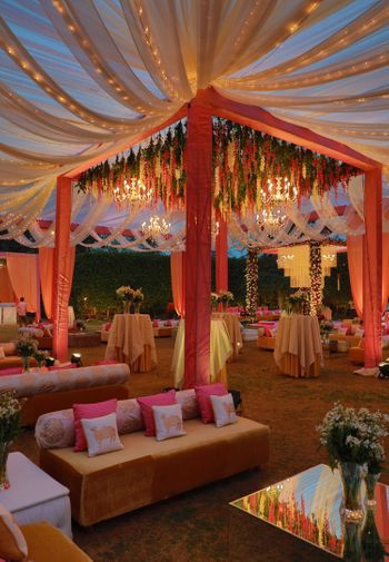Photo of Red and gold mandap with hanging florals