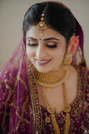 Bride wearing a deep pink lehenga with gold jewellery.