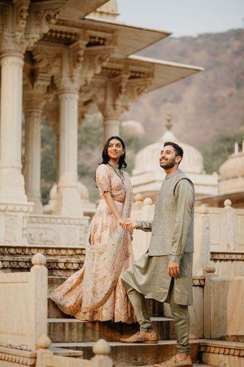 Bride and groom posing against a royal palace.