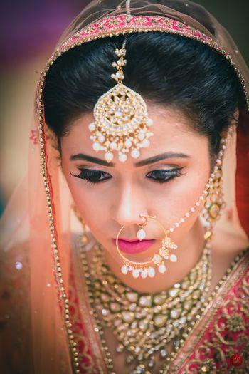 Bridal maangtikka and matching nath with pearls