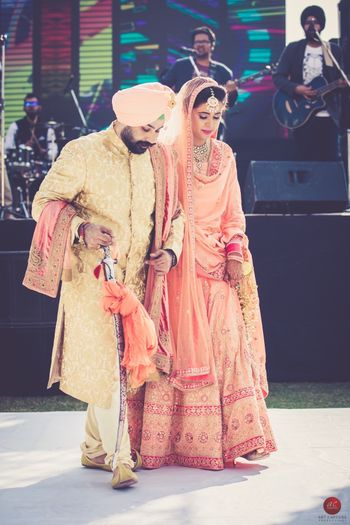 Coordinated bride and groom in peach wedding outfit and turban