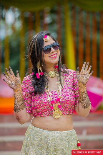 Bride in pink wearing shades and pompom gota jewellery