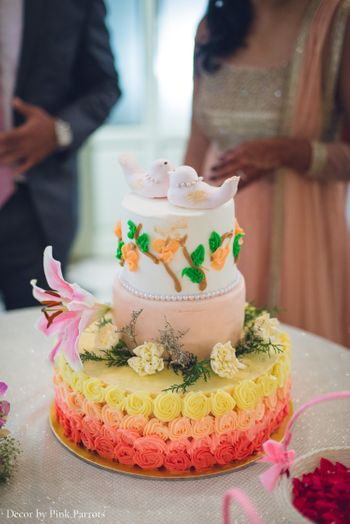 White and orange ombre wedding cake with birds as cake topper